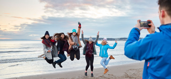 students jumping on a beach